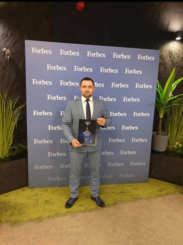 Businessman standing with Forbes Diamonds award for C2C sp. z o. o.